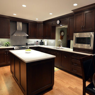 Inspiration for a mid-sized transitional l-shaped medium tone wood floor enclosed kitchen remodel in Chicago with an undermount sink, recessed-panel cabinets, dark wood cabinets, quartz countertops, gray backsplash, porcelain backsplash, stainless steel appliances and an island