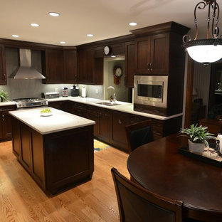 Example of a mid-sized transitional l-shaped medium tone wood floor enclosed kitchen design in Chicago with an undermount sink, recessed-panel cabinets, dark wood cabinets, quartz countertops, gray backsplash, porcelain backsplash, stainless steel appliances and an island