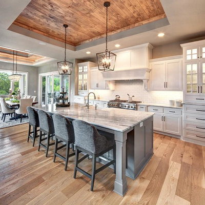 Example of a classic light wood floor and beige floor eat-in kitchen design in Kansas City with a farmhouse sink, white cabinets, white backsplash, subway tile backsplash, stainless steel appliances, an island, gray countertops and shaker cabinets