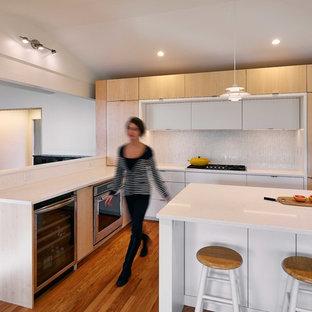 Idéer för att renovera ett mellanstort 50 tals vit vitt l-kök, med släta luckor, skåp i ljust trä, bänkskiva i koppar, vitt stänkskydd, stänkskydd i keramik, rostfria vitvaror, en köksö och mellanmörkt trägolv