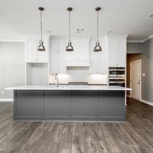リトルロックの中くらいのモダンスタイルのおしゃれなキッチン (アンダーカウンターシンク、シェーカースタイル扉のキャビネット、白いキャビネット、クオーツストーンカウンター、白いキッチンパネル、サブウェイタイルのキッチンパネル、シルバーの調理設備、濃色無垢フローリング、茶色い床、白いキッチンカウンター) の写真