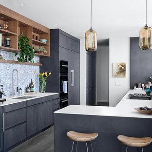 Foto di una cucina a L minimalista con lavello a doppia vasca, ante lisce, ante nere, paraspruzzi multicolore, elettrodomestici da incasso, penisola, pavimento marrone e top bianco