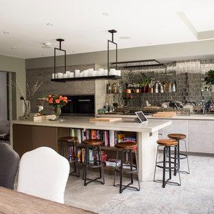 На фото: линейные кухни среднего размера в современном стиле с обеденным столом, врезной раковиной, плоскими фасадами, серыми фасадами, столешницей из известняка, фартуком из зеркальной плитки, техникой под мебельный фасад, полуостровом и серым полом