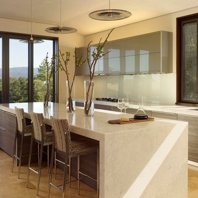 Inspiration for a contemporary galley kitchen remodel in San Francisco with a single-bowl sink, flat-panel cabinets, gray cabinets, white backsplash and glass sheet backsplash