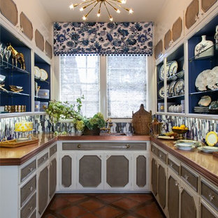 На фото: маленькая п-образная кухня в классическом стиле с кладовкой, открытыми фасадами, столешницей из меди, полом из терракотовой плитки, монолитной раковиной, синим фартуком и фартуком из стеклянной плитки без острова