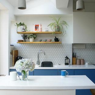 Foto di una cucina design di medie dimensioni con lavello a vasca singola, ante lisce, ante blu, paraspruzzi bianco e top bianco