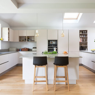This is an example of a large contemporary u-shaped kitchen in London with a double-bowl sink, flat-panel cabinets, white cabinets, an island, grey worktops, concrete worktops, black appliances, light hardwood flooring and beige floors.