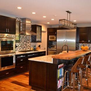 ボルチモアの大きいエクレクティックスタイルのおしゃれなキッチン (エプロンフロントシンク、落し込みパネル扉のキャビネット、濃色木目調キャビネット、御影石カウンター、グレーのキッチンパネル、メタルタイルのキッチンパネル、シルバーの調理設備の、淡色無垢フローリング、黄色い床、白いキッチンカウンター) の写真