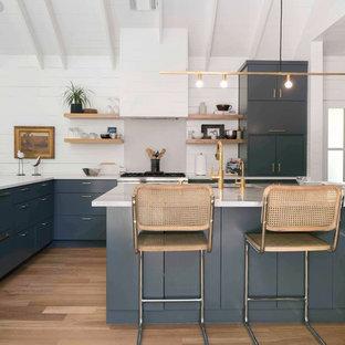 オースティンのトランジショナルスタイルのおしゃれなコの字型キッチン (フラットパネル扉のキャビネット、中間色木目調キャビネット、白いキッチンパネル、サブウェイタイルのキッチンパネル、シルバーの調理設備、濃色無垢フローリング、茶色い床) の写真