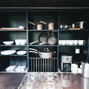 Esempio di una cucina minimal di medie dimensioni con lavello sottopiano, ante lisce, ante marroni, top in marmo, paraspruzzi nero, paraspruzzi in legno, elettrodomestici in acciaio inossidabile, pavimento con piastrelle in ceramica, isola, pavimento nero e top nero