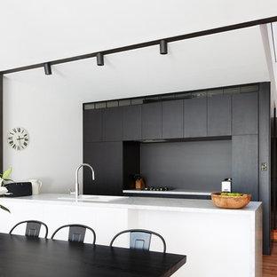 シドニーのモダンスタイルのおしゃれなキッチン (ダブルシンク、フラットパネル扉のキャビネット、黒いキャビネット、グレーのキッチンパネル、無垢フローリング、赤い床) の写真