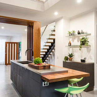 Small modern open concept kitchen pictures - Open concept kitchen - small modern galley concrete floor and gray floor open concept kitchen idea in Brisbane with flat-panel cabinets, gray cabinets, stainless steel countertops, glass sheet backsplash, stainless steel appliances and an island