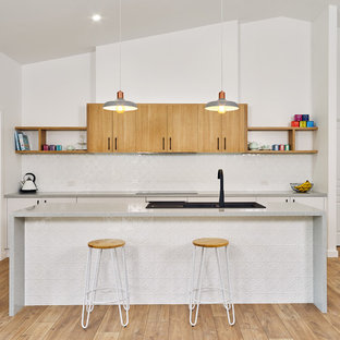 This is an example of a mid-sized contemporary galley open plan kitchen in Other with a drop-in sink, flat-panel cabinets, light wood cabinets, quartz benchtops, white splashback, black appliances, laminate floors, with island, brown floor and grey benchtop.