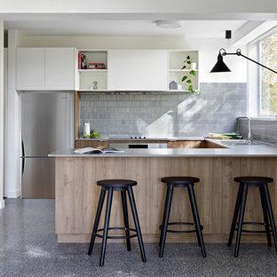 Small contemporary u-shaped kitchen in Melbourne with a double-bowl sink, medium wood cabinets, quartz benchtops, grey splashback, ceramic splashback, stainless steel appliances, concrete floors, grey floor, grey benchtop, flat-panel cabinets and a peninsula.