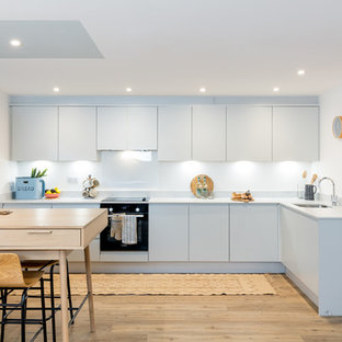 This is an example of a scandinavian l-shaped kitchen/diner in Dorset with a submerged sink, flat-panel cabinets, white cabinets, white splashback, black appliances, light hardwood flooring, no island, beige floors and white worktops.