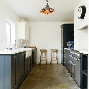 他の地域の小さいラスティックスタイルのおしゃれなキッチン (エプロンフロントシンク、シェーカースタイル扉のキャビネット、青いキャビネット、人工大理石カウンター、白いキッチンパネル、サブウェイタイルのキッチンパネル、黒い調理設備、トラバーチンの床、アイランドなし) の写真