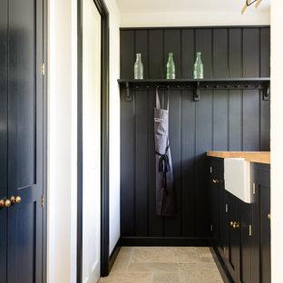 他の地域の小さいラスティックスタイルのおしゃれなI型キッチン (エプロンフロントシンク、シェーカースタイル扉のキャビネット、木材カウンター、トラバーチンの床、黒いキャビネット) の写真