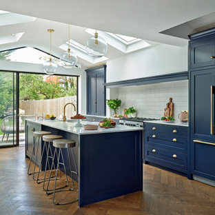 Photo of a large traditional galley kitchen/diner in London with a belfast sink, shaker cabinets, blue cabinets, quartz worktops, white splashback, ceramic splashback, integrated appliances, an island, white worktops, a vaulted ceiling, medium hardwood flooring and brown floors.