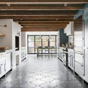 オーランドの中サイズのエクレクティックスタイルのおしゃれなキッチン (エプロンフロントシンク、シェーカースタイル扉のキャビネット、青いキャビネット、人工大理石カウンター、白いキッチンパネル、セラミックタイルのキッチンパネル、シルバーの調理設備、コンクリートの床、アイランドなし、グレーの床) の写真