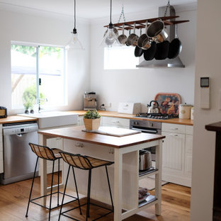 Inspiration for a small transitional l-shaped separate kitchen in Perth with a farmhouse sink, raised-panel cabinets, white cabinets, wood benchtops, stainless steel appliances, medium hardwood floors, with island and brown floor.