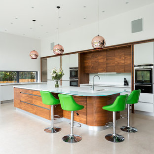 Photo of a medium sized contemporary l-shaped kitchen in Other with a submerged sink, flat-panel cabinets, white cabinets, white splashback, glass sheet splashback, black appliances, an island, beige floors and white worktops.