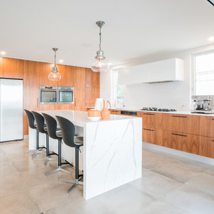 Large contemporary l-shaped kitchen in Sydney with flat-panel cabinets, medium wood cabinets, stainless steel appliances, with island, grey floor and white benchtop.