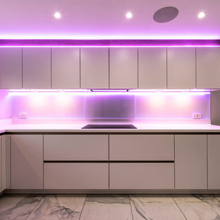 Mid-sized contemporary l-shaped eat-in kitchen in Manchester with a double-bowl sink, flat-panel cabinets, white cabinets, solid surface benchtops, grey splashback, glass sheet splashback, black appliances, porcelain floors, white floor and white benchtop.