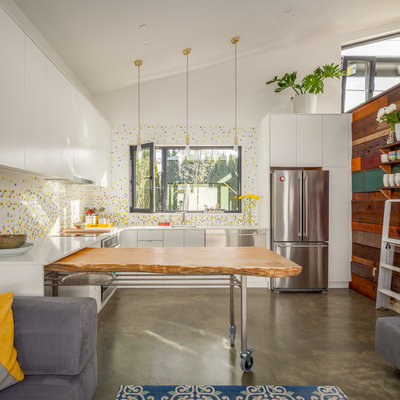Large trendy l-shaped concrete floor and gray floor eat-in kitchen photo in Vancouver with flat-panel cabinets, white cabinets, mosaic tile backsplash, stainless steel appliances, an island, a single-bowl sink, quartz countertops, multicolored backsplash and white countertops