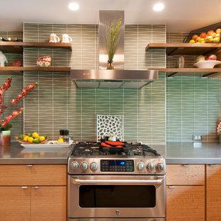 Foto de cocina en U, retro, con armarios con paneles lisos, puertas de armario de madera clara, encimera de acero inoxidable, salpicadero gris, salpicadero de azulejos de vidrio y electrodomésticos de acero inoxidable