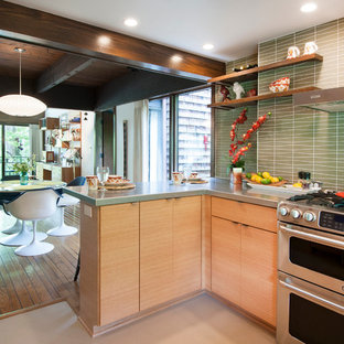Design ideas for a small midcentury u-shaped open plan kitchen in Columbus with an integrated sink, flat-panel cabinets, light wood cabinets, stainless steel benchtops, green splashback, glass tile splashback, stainless steel appliances, linoleum floors and a peninsula.