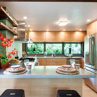 Inspiration för små 50 tals kök, med en integrerad diskho, släta luckor, skåp i ljust trä, bänkskiva i rostfritt stål, grönt stänkskydd, stänkskydd i glaskakel, rostfria vitvaror, linoleumgolv och en halv köksö
