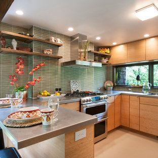 Photo of a small midcentury u-shaped open plan kitchen in Columbus with an integrated sink, flat-panel cabinets, light wood cabinets, stainless steel benchtops, green splashback, glass tile splashback, stainless steel appliances, linoleum floors and a peninsula.