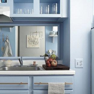 Diseño de cocina lineal, de estilo americano, pequeña, cerrada, sin isla, con fregadero encastrado, armarios estilo shaker, puertas de armario azules, encimera de laminado, salpicadero metalizado, salpicadero con efecto espejo y electrodomésticos blancos