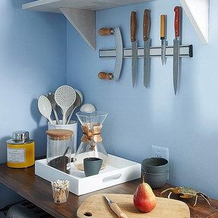 Diseño de cocina lineal, de estilo americano, pequeña, cerrada, sin isla, con fregadero encastrado, armarios estilo shaker, puertas de armario azules, encimera de laminado, salpicadero metalizado, salpicadero con efecto espejo, electrodomésticos blancos y suelo de corcho