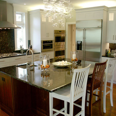 Eat-in kitchen - mid-sized traditional l-shaped medium tone wood floor eat-in kitchen idea in Milwaukee with shaker cabinets, white cabinets, stainless steel appliances, a single-bowl sink, marble countertops, black backsplash, an island and stone slab backsplash
