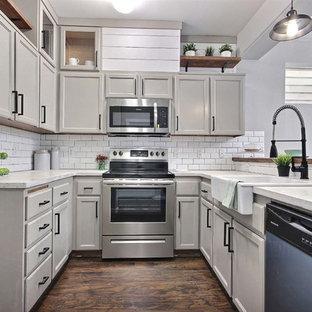 Modelo de cocina en U, ecléctica, pequeña, con fregadero sobremueble, puertas de armario beige, encimera de cemento, salpicadero blanco, salpicadero de azulejos tipo metro, suelo laminado y suelo marrón