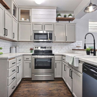 Small eclectic u-shaped kitchen in Seattle with a farmhouse sink, beige cabinets, concrete benchtops, white splashback, subway tile splashback, laminate floors and brown floor.