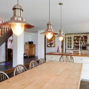 Diseño de cocina comedor en L, de estilo de casa de campo, grande, sin isla, con fregadero sobremueble, armarios abiertos, puertas de armario blancas, encimera de madera, electrodomésticos con paneles y suelo de baldosas de porcelana