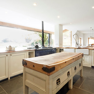 Example of a large farmhouse l-shaped porcelain floor eat-in kitchen design in Wiltshire with a farmhouse sink, open cabinets, white cabinets, wood countertops, paneled appliances and no island