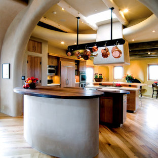 Southwestern kitchen remodeling - Inspiration for a southwestern bamboo floor kitchen remodel in Albuquerque with flat-panel cabinets, medium tone wood cabinets, wood countertops, paneled appliances and two islands