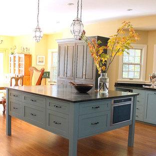 Modelo de cocina en L, de estilo de casa de campo, de tamaño medio, abierta, con fregadero sobremueble, armarios estilo shaker, puertas de armario azules, encimera de granito, salpicadero amarillo, electrodomésticos negros, suelo de madera oscura y una isla