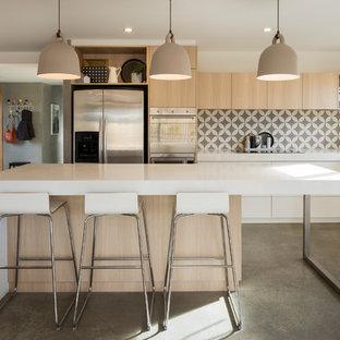 キャンベラのコンテンポラリースタイルのおしゃれなキッチン (アンダーカウンターシンク、フラットパネル扉のキャビネット、淡色木目調キャビネット、ベージュキッチンパネル、シルバーの調理設備の、グレーの床) の写真