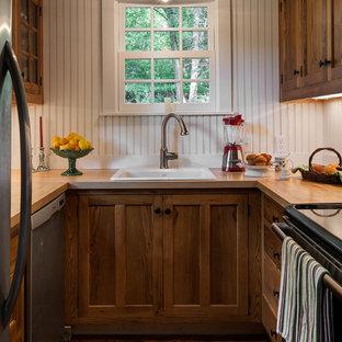 Imagen de cocina en U, clásica, pequeña, cerrada, con fregadero encastrado, armarios con paneles empotrados, puertas de armario de madera en tonos medios, encimera de madera y electrodomésticos de acero inoxidable
