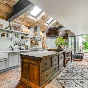 Offene, Zweizeilige, Mittelgroße Tropenstil Küche mit Landhausspüle, Schrankfronten im Shaker-Stil, grauen Schränken, Arbeitsplatte aus Holz, Küchenrückwand in Weiß, Rückwand aus Backstein, braunem Holzboden, Kücheninsel, braunem Boden und brauner Arbeitsplatte in London