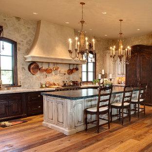 ワシントンD.C.の地中海スタイルのおしゃれなコの字型キッチン (レイズドパネル扉のキャビネット、ヴィンテージ仕上げキャビネット、パネルと同色の調理設備) の写真