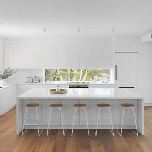 Inspiration for a beach style l-shaped kitchen in Sydney with an undermount sink, flat-panel cabinets, white cabinets, window splashback, panelled appliances, medium hardwood floors, with island and white benchtop.