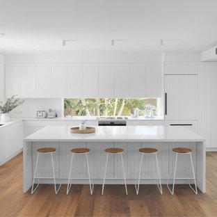 シドニーのビーチスタイルのおしゃれなキッチン (アンダーカウンターシンク、フラットパネル扉のキャビネット、白いキャビネット、ガラスまたは窓のキッチンパネル、パネルと同色の調理設備、無垢フローリング、白いキッチンカウンター) の写真