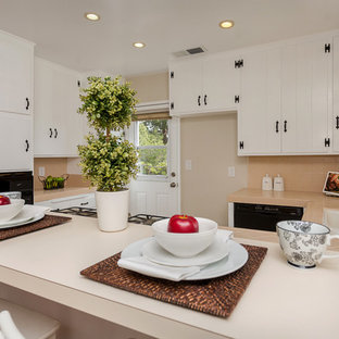 Mid-sized traditional u-shaped kitchen in Los Angeles with an undermount sink, louvered cabinets, white cabinets, glass benchtops, beige splashback, glass tile splashback, black appliances, ceramic floors and a peninsula.