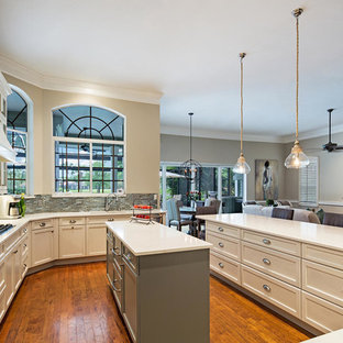 Large transitional open concept kitchen designs - Inspiration for a large transitional u-shaped open concept kitchen remodel in Tampa with recessed-panel cabinets, white cabinets, quartz countertops, metallic backsplash, glass tile backsplash, paneled appliances and an island