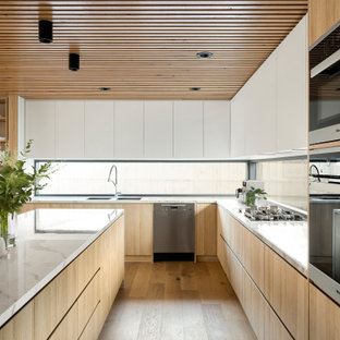 This is an example of a large contemporary l-shaped open plan kitchen in Melbourne with an undermount sink, flat-panel cabinets, light wood cabinets, marble benchtops, window splashback, black appliances, light hardwood floors, with island, brown floor, white benchtop and timber.